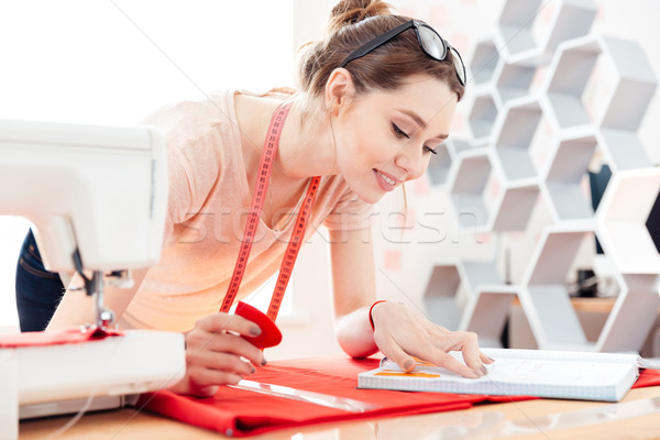 Happy woman seamstress at work with red fabric Stock photo © deandrobot