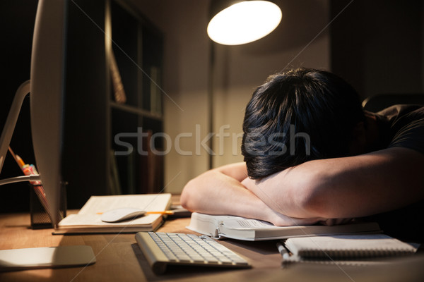 Exhausted man studying and sleeping on table in dark room  Stock photo © deandrobot