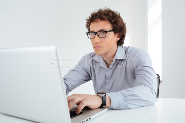 Businessman working on laptop computer in office Stock photo © deandrobot