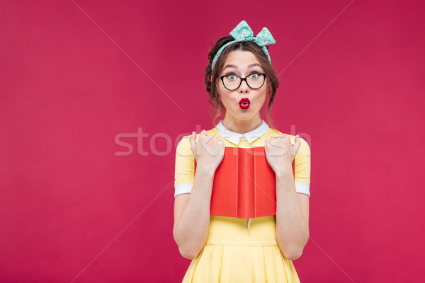 Surprised pinup girl in glasses standing and holding red book Stock photo © deandrobot