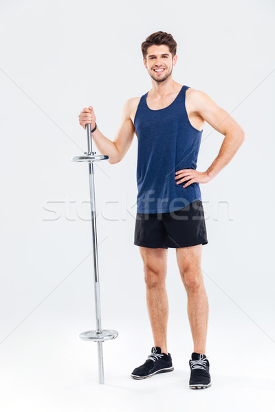 Full length portrait of a happy sportsman standing with barbell Stock photo © deandrobot