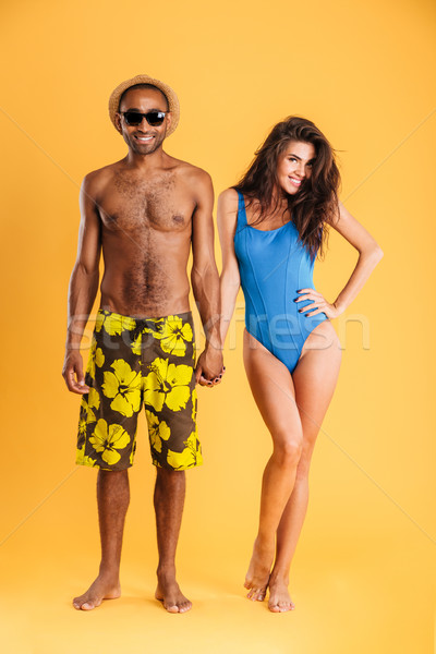 Young beautiful loving couple in beachwear holding hands Stock photo © deandrobot