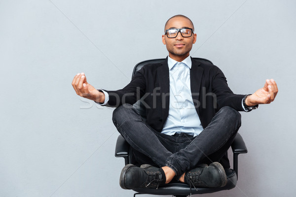 Attractive young man in glasses meditating on office chair Stock photo © deandrobot