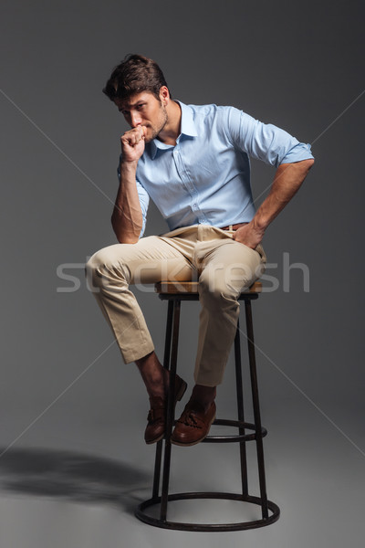 Attractive young man in blue shirt sitting on chair Stock photo © deandrobot