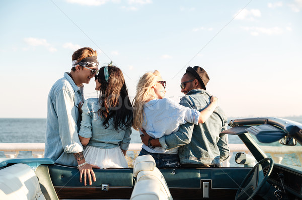 Back view of two couples embracing near cabriolet Stock photo © deandrobot