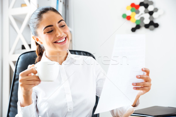 Happy smiling businesswoman analysing documents while having coffee break Stock photo © deandrobot