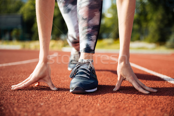 Cropped image of a female sprinter getting ready to run Stock photo © deandrobot