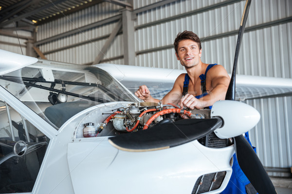 Cheerful young air mechanic working with small plane Stock photo © deandrobot