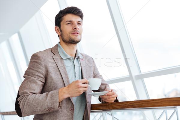 задумчивый молодые бизнесмен куртка чашку кофе Сток-фото © deandrobot