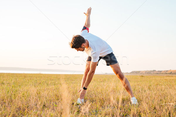 Young sportsman standing and stretching in the morning Stock photo © deandrobot