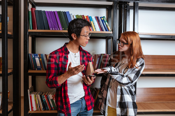 Redhead girl talking and arguing with asian boy in library Stock photo © deandrobot