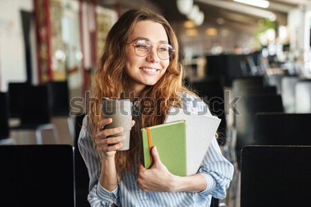Smiling beautiful young woman drinking coffee in outdoor cafe Stock photo © deandrobot