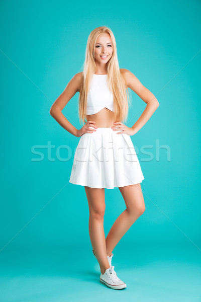 Smiling lovely woman standing with hands on hips Stock photo © deandrobot