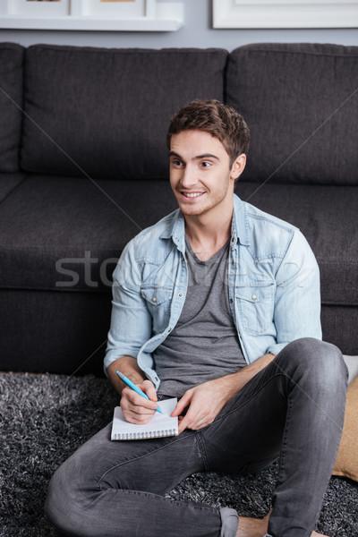 Mann stellt fest Schönschreibheft Sitzung Teppich Stock foto © deandrobot