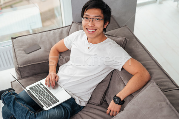 Above portrait of asian man with laptop on sofa Stock photo © deandrobot