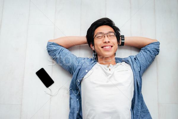 Asian man in shirt on the floor Stock photo © deandrobot