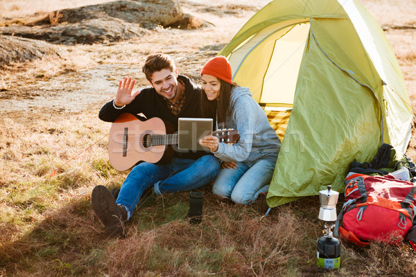 Smiling couple with guitar near the tent Stock photo © deandrobot