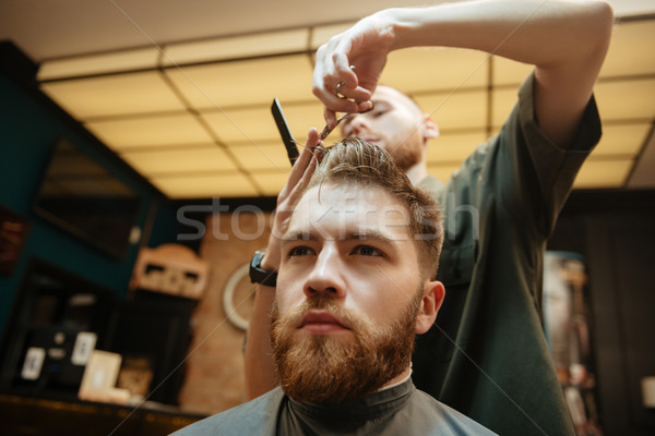 Man getting haircut by hairdresser with scissors Stock photo © deandrobot