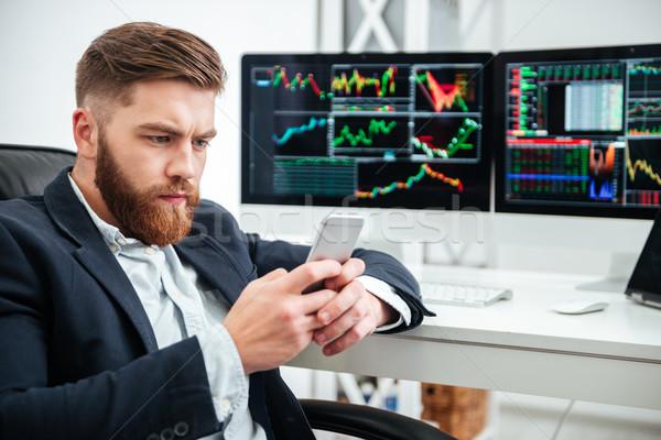 Sério empresário sessão telefone móvel escritório barbudo Foto stock © deandrobot