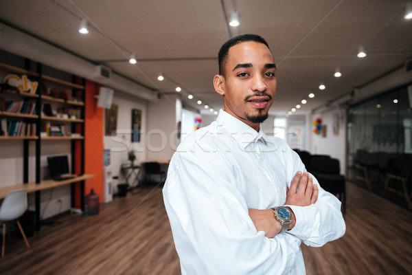 African cheerful businessman standing in library Stock photo © deandrobot