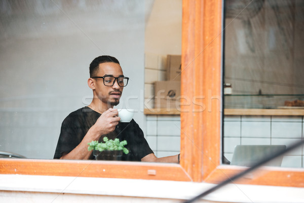 Portrait of a young african man drinking coffee Stock photo © deandrobot