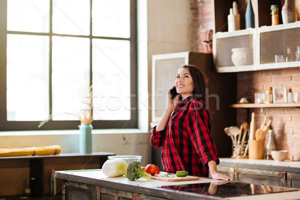 Woman talking on phone in kitchen Stock photo © deandrobot
