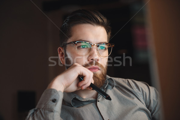 Serious designer working late at night and looking to computer. Stock photo © deandrobot