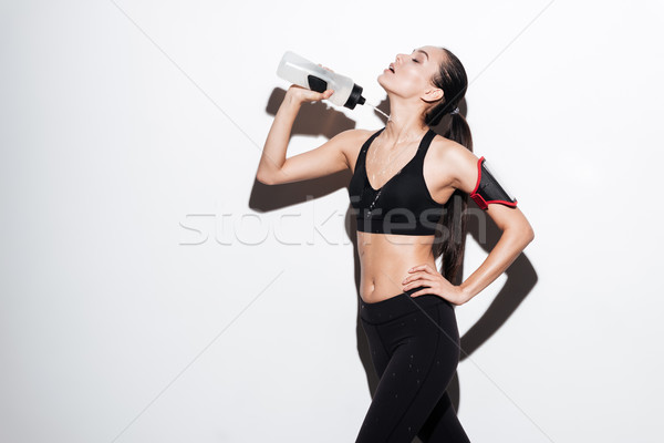 Seductive young sportswoman pouring water from bottle on herself Stock photo © deandrobot