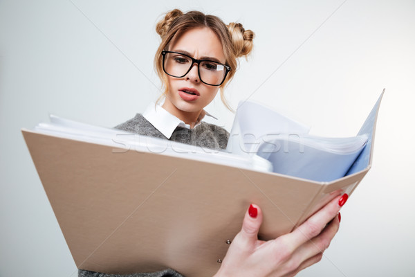 Serious frowning young woman in glasses reading documents in folder Stock photo © deandrobot