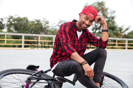 Cheerful dark skinned man standing near his bicycle Stock photo © deandrobot