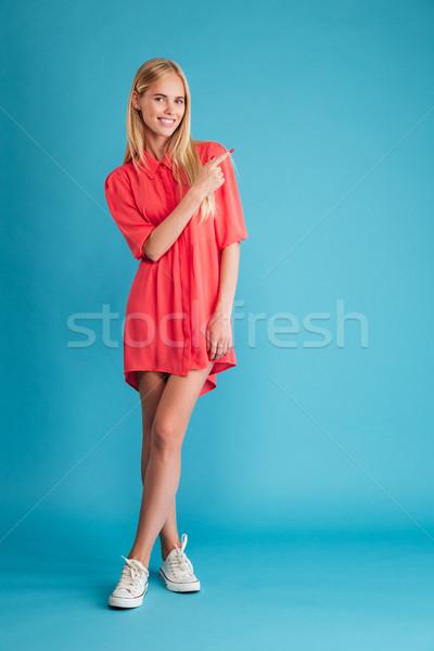 Mutlu kadın kırmızı elbise ayakta işaret parmak Stok fotoğraf © deandrobot