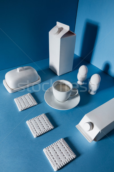 Top view of milk packs, eggs, cup, butter and cookies Stock photo © deandrobot