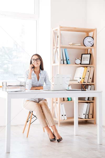 Businesswoman sitting in her office and talking by phone Stock photo © deandrobot