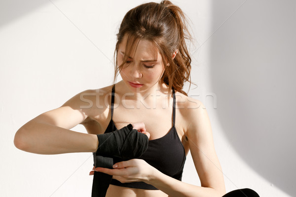 Serious woman wrapping hands with black boxing bandage Stock photo © deandrobot