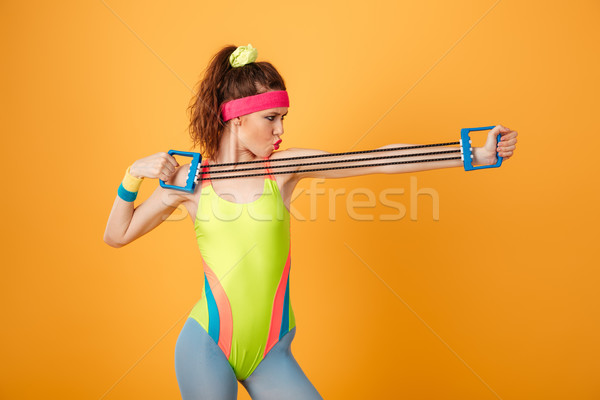 Serious focused young fitness woman standing and training with expander Stock photo © deandrobot
