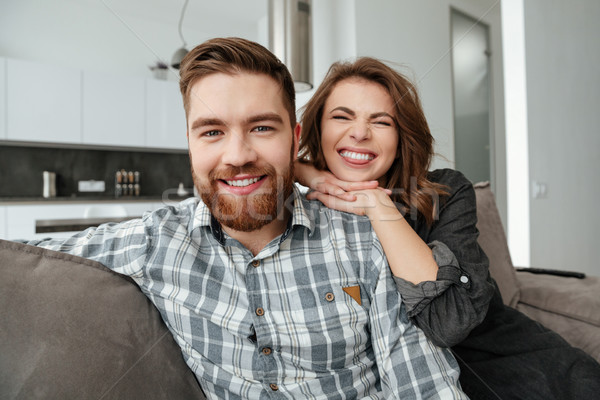Young funny loving couple sitting on sofa indoors Stock photo © deandrobot