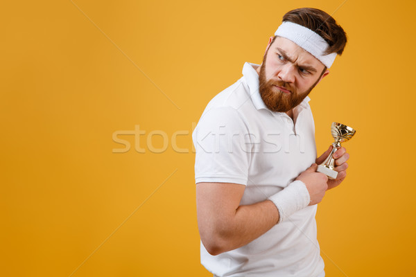 Angry young sportsman with reward looking away. Stock photo © deandrobot