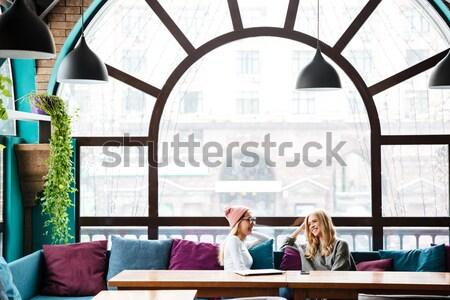 Due sorridere donne parlando tavola cafe Foto d'archivio © deandrobot