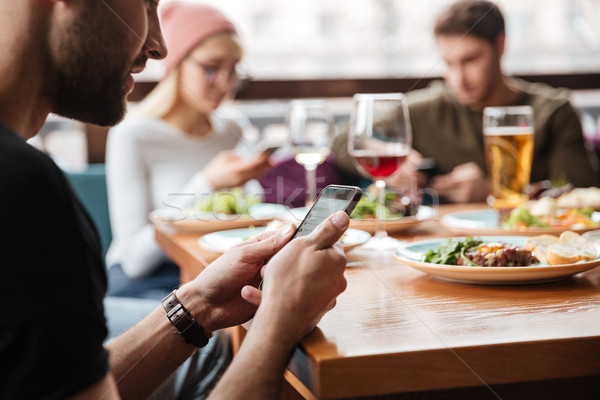 Stock photo: Friends sitting in cafe and using mobile phones