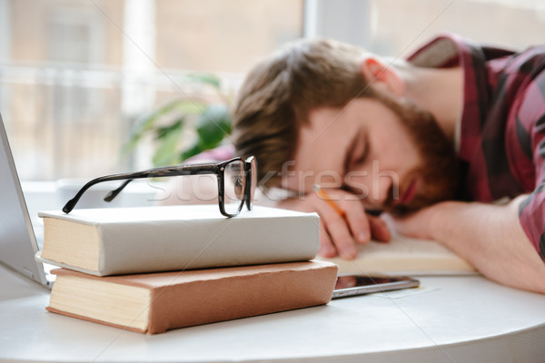 Sleeping bearded young man student lies on hands Stock photo © deandrobot