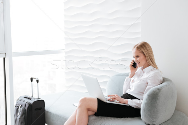 Pretty business woman using laptop and talking by phone. Stock photo © deandrobot