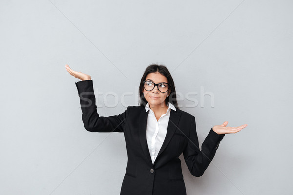 Serious businesswoman in eyeglasses holding copyspace on two palms Stock photo © deandrobot
