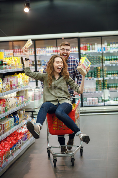 Couple having fun with the shopping cart in the supermarket Stock photo © deandrobot