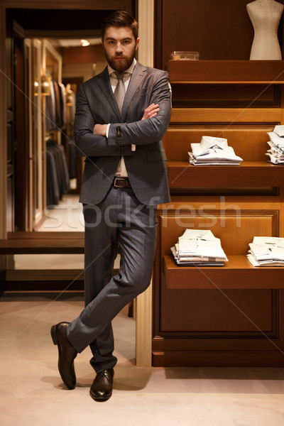Vertical image of serious man standing with crossed arms Stock photo © deandrobot