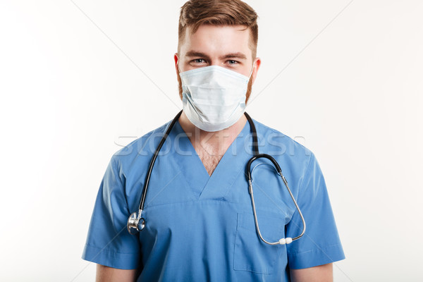 Portrait of a male surgeon wearing stethoscope and mask Stock photo © deandrobot
