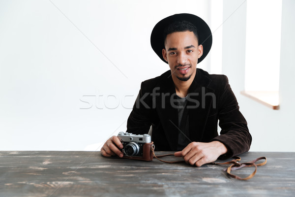 Smiling African man sitting by the table Stock photo © deandrobot