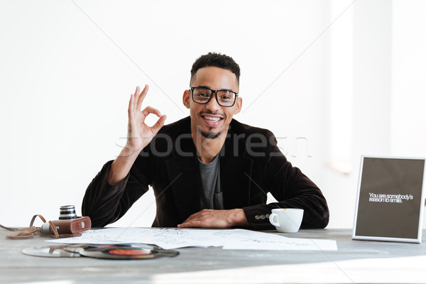 African man sitting by the table and showing ok sign Stock photo © deandrobot