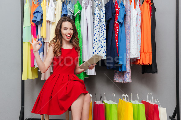 Woman with tablet near hanger Stock photo © deandrobot