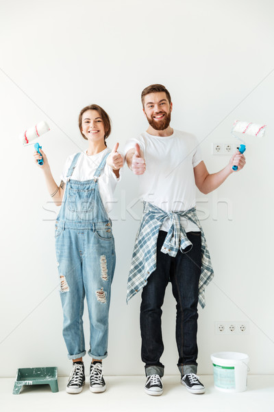 Happy lovers showing thumb up while making repair Stock photo © deandrobot