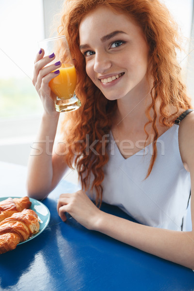 Smiling redhead lady sitting at the table drinking juice Stock photo © deandrobot